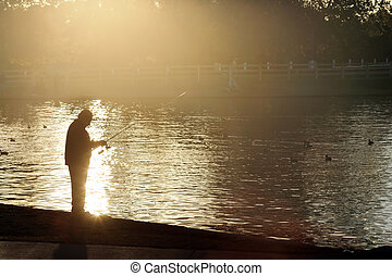 Silhouette of a man fishing at sunset