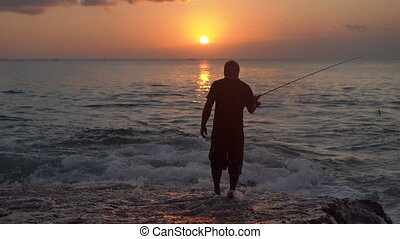 Silhouette of a man fishing in a sea with a fishing pole during sunset.