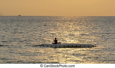 Silhouette of a man fishing on the displacer at Sunset. Pattaya, Thailand