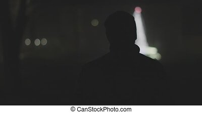 silhouette of a man from the back in a foggy night city