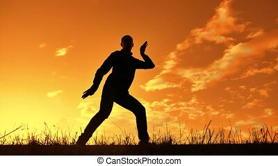 silhouette of a man funny dancing at sunset nature sunlight....