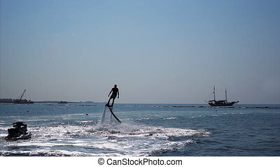 Silhouette of a Man Having Fun on Flyboard in the Sea.
