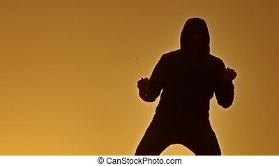 silhouette of a man in a hood with a knife lifestyle. Shadow...