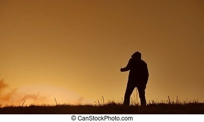 silhouette of a man in a hood with a knife. Shadow blur of horror man in jacket with hood facing side body and show the knife in his hand. A dangerous thug with a knife lifestyle killer bandit