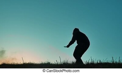 silhouette of a man in a hood with a knife. Shadow blur of horror man in jacket with hood facing side body and show the knife in his hand lifestyle. A dangerous thug with a knife killer bandit