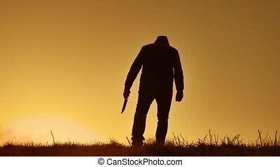 silhouette of a man in a hood with a knife. Shadow blur of horror man in jacket with hood facing side lifestyle body and show the knife in bandit his hand. A dangerous thug with a knife killer