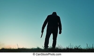 silhouette of a man in hood with a knife. Shadow blur of horror man in jacket with hood facing side lifestyle body and show the knife in his hand. bandit A dangerous thug with a knife killer