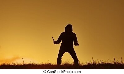 silhouette of a man in a hood with a knife. Shadow blur of horror man in jacket with hood facing side lifestyle body and show the knife in his hand. A dangerous thug with a knife killer bandit