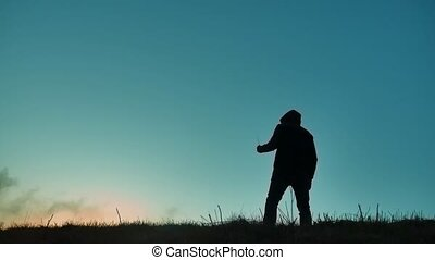 silhouette of a man in a hood with a knife. Shadow blur of horror man in jacket with hood facing side body and show the knife in his hand. A dangerous thug with a knife killer bandit lifestyle