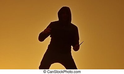 silhouette of a man in a hood with a knife. Shadow lifestyle blur of horror man in jacket with hood facing side body and show the knife bandit in his hand. A dangerous thug with a knife killer