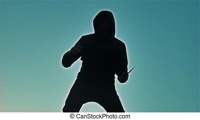 silhouette of a man in a hood with lifestyle a knife. Shadow blur of horror man in jacket with hood facing side body and show the knife bandit in his hand. A dangerous thug with a knife killer