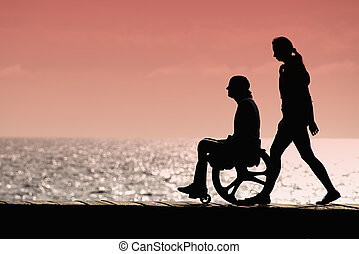 Silhouette of a man in a wheelchair with a woman at sunset at sea