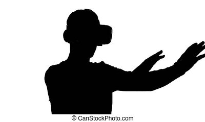 silhouette of a man in virtual reality glasses watching a video