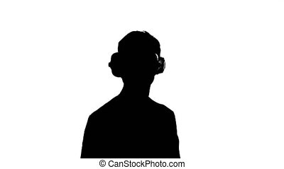 silhouette of a man in virtual reality glasses watching a...