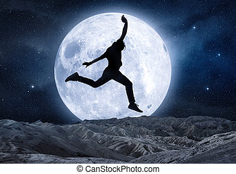 silhouette of a man jumping in front of full moon