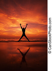 Silhouette of a man Jumping in the air on a beach