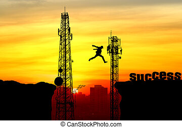 Silhouette of a man jumping over the cliff and Telecommunication tower