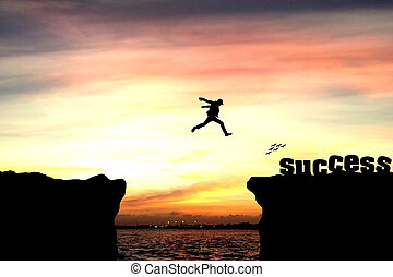 Silhouette of a man jumping over the cliff