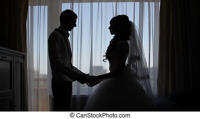 Silhouette of a man kissing hands of woman on a window background