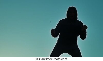 silhouette of a man lifestyle in a hood with a knife. Shadow blur of horror man in jacket with hood facing side body and show the knife in bandit his hand. A dangerous thug with a knife killer