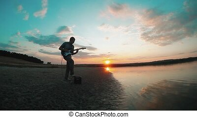 silhouette of a man musician guitarist playing an electric guitar at sunset near the water. male guitarist concept musician lifestyle