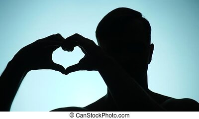 silhouette of a man on a colored background, doing a heart...