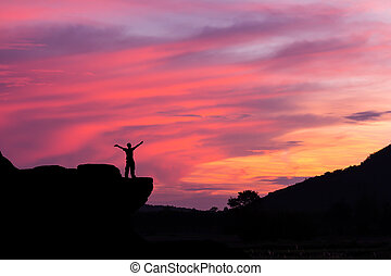 Silhouette of a man on the rock at sunset