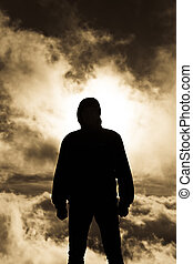 Persistent man silhouette with gloomy clouds as background