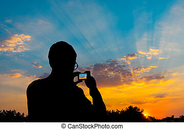 Silhouette of a man photographing the sunset on a smartphone.