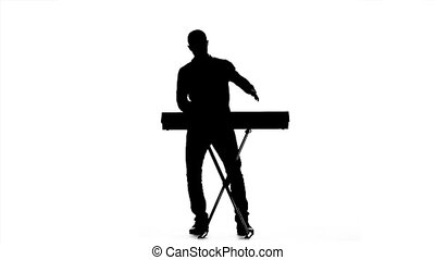 Silhouette of a man playing the piano. Slow motion