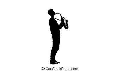 Silhouette of a man playing the saxophone standing sideways...