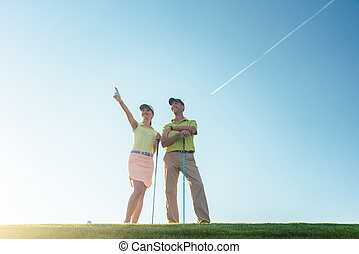 Silhouette of a man pointing while standing next to his partner