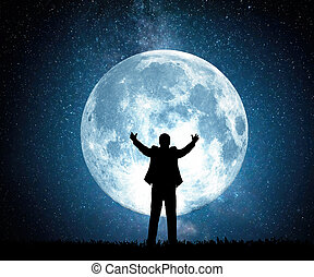 Silhouette of a man pulling his arms up on the background of the moon and the starry sky.