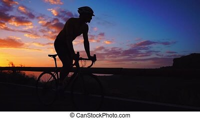 Silhouette of a man riding a Bicycle at sunset on a mountain...
