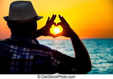 silhouette of a Man showing love with fingers in the sunset
