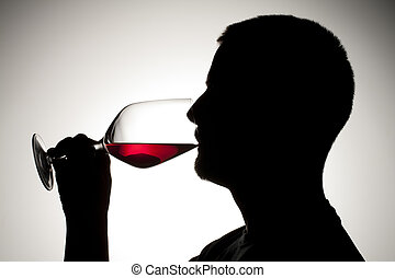 silhouette of a man sipping wine