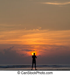 Silhouette of a Man standing at sunrise