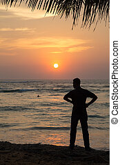 Silhouette of a man standing on sandy beach at sunset.