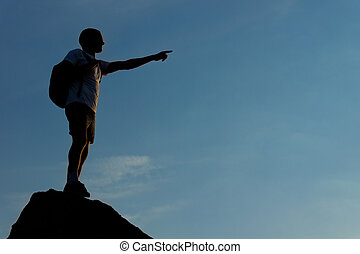 Silhouette of a man standing on the mountain top