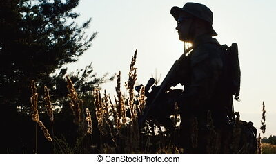 Silhouette of a man takes aim. Airsoft game