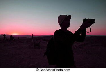 Silhouette of a man taking photo against blue and pink sunset sky
