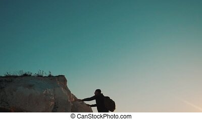 silhouette of a man tourist climbs up the mountain to the...