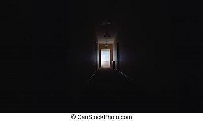 Silhouette of a man walking along a dark corridor