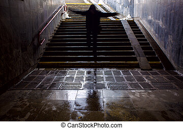silhouette of a man walking his hands up in the subway