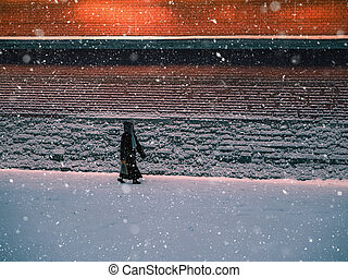 Silhouette of a man walking in the snow in the evening at the red wall