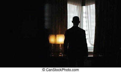 Silhouette of a Man wearing suit walking from a dark room towards a bright window in slow motion. Man stops, puts his hands on a table and looks pensive to the window.