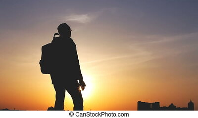 Silhouette of a man with a backpack against bright sky sunset