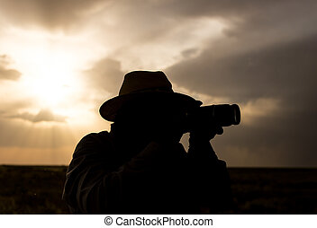 silhouette of a man with a camera on a sunset background