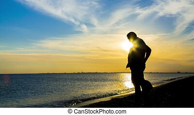 Silhouette Of a Man With a Child On Sea Background