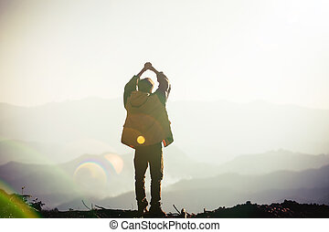 Silhouette of a man with hands raised in the sunset concept for religion, worship, prayer and praise